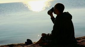 Young man drinking from cup on a beach stock footage