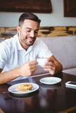 Young man drinking cup of coffee and pastry beside Stock Photography
