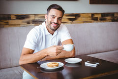 Young man drinking cup of coffee and pastry beside Stock Images