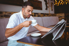 Young man drinking cup of coffee reading newspaper. At the cafe Royalty Free Stock Photos