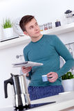 Young man drinking an espresso and reading the newspaper Stock Photography