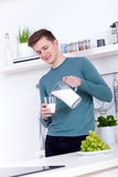 Young man drinking a glass of milk in the kitchen Royalty Free Stock Photography