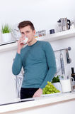 Young man drinking a glass of milk in the kitchen Stock Image