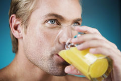 A young man drinking a glass of orange juice Royalty Free Stock Photos