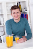 Young man drinking a glass of orange juice Stock Image