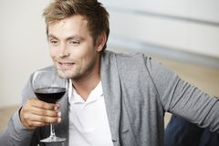 Young man drinking a glass of redwine. Mid adult man relaxing with glass of red wine Stock Photos