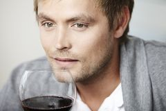 Young man drinking a glass of redwine. Mid adult man relaxing with glass of red wine Royalty Free Stock Photography
