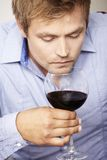 Young man drinking a glass of redwine. Mid adult man smelling red wine Royalty Free Stock Images