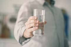 Young man drinking glass of water Stock Images