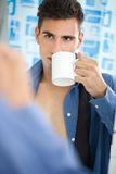 Young man drinking his morning coffee Stock Image