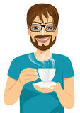 Young man drinking hot coffee or tea Stock Photos