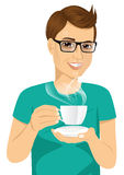 Young man drinking hot coffee or tea Royalty Free Stock Photos