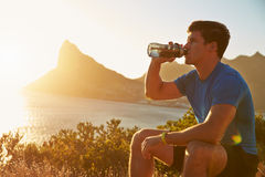 Young man drinking after jogging Stock Photo