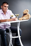 Young man drinking martini with teddy bear Stock Photos