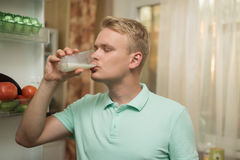 Young man drinking milk in the kitchen, standing at the fridge Royalty Free Stock Photography