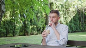 A Young Man Drinking Milkshake in the Park. A young man sitting at the table and drinking a milkshake in the park. Medium shot. Soft Focus royalty free stock image