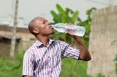 Young man drinking mineral water. This young man is trying to quench their thirst with a large bottle of mineral water royalty free stock photos
