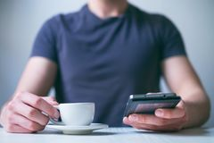 Young man drinking morning coffee and holding mobile phone. Coffee break. Man holding cup of fresh roasted coffee and looking at t Royalty Free Stock Image
