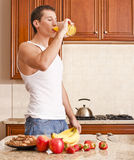 Young Man Drinking Orange Juice. Young man wearing tank top and jeans in kitchen drinking a glass of orange juice. Vertical shot Stock Photos