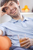 Young man drinking orange juice Stock Photography