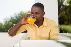 Young man drinking orange juice while looking at laptop. In cafe Royalty Free Stock Photos