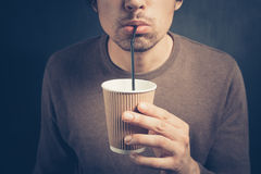 Young man drinking from paper cup with straw Stock Photo