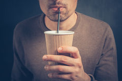 Young man drinking from paper cup with straw Royalty Free Stock Photo