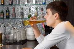 Young man drinking a pint of draught beer. Close up side view of a young man drinking a pint of draught beer while sitting at the counter in a bar, pub, or Royalty Free Stock Photography
