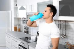 Young man drinking protein shake. In kitchen stock photos