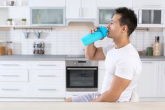 Young man drinking protein shake in kitchen. Space for text royalty free stock image