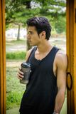 Young man drinking protein shake in outdoor gym. Attractive young man drinking protein shake in outdoor gym in city park royalty free stock images