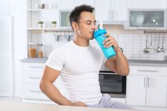 Young man drinking protein shake. In kitchen royalty free stock images
