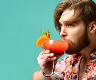 Young man drinking red orange margarita cocktail drink juice happy looking at camera over blue mint Stock Photos