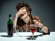 Young man drinking red wine and feeling despair. Photo of youth addicted to alcohol, alcoholism concept, social problem Stock Photo