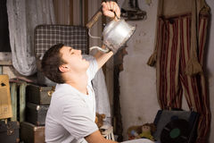 Young Man Drinking Something From Vintage Kettle Royalty Free Stock Photos