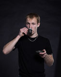 Young man drinking tea on a black Stock Photography