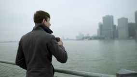Young man drinking tea and enjoying view on Manhattan near Hudson river stock footage