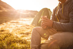 Young man drinking tea at sunrise in mountains. Royalty Free Stock Image