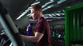 Young man drinking water from a bottle during cardio workout. stock video