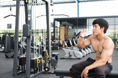 Young man drinking water in fitness center. male athlete feeling. Thirsty after training in gym. sporty asian guy taking a break from working out in health club stock images