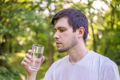 Young man is drinking water from glass in nature stock images