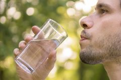 Young man is drinking water from glass in nature at sunny hot day Royalty Free Stock Photos