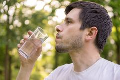 Young man is drinking water from glass in nature at sunny hot day Stock Photos