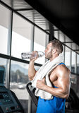 Young man drinking water in gym Stock Photography