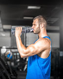 Young man drinking water in gym Stock Photo