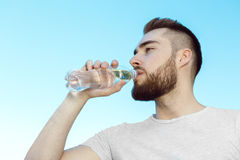 Young man drinking water, hot day Royalty Free Stock Photo