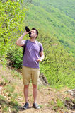 Young man Drinking Water in the mountain Stock Photos