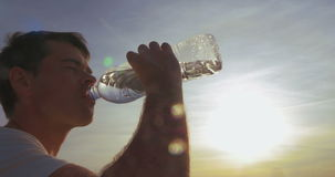 Young man drinking water outdoor at sunset stock footage