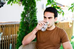 Young man drinking water while sitting at cafe. Garden stock photo