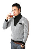 Young man drinking whiskey from a glass. Isolated Stock Photography